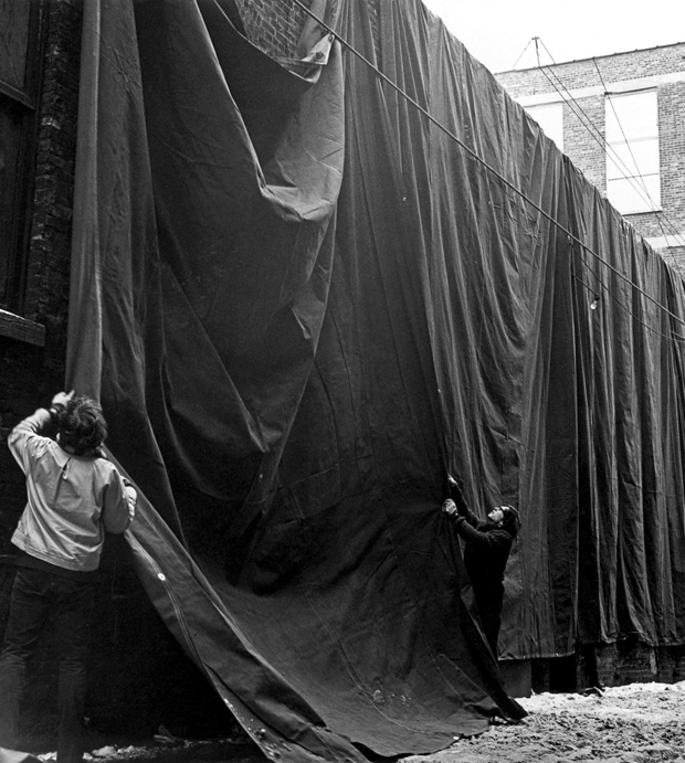 Christo and an assistant adjust the draping of one of the heavy sheets of tarpaulin suspended from the roof of the MCA. (Harry Shunk)