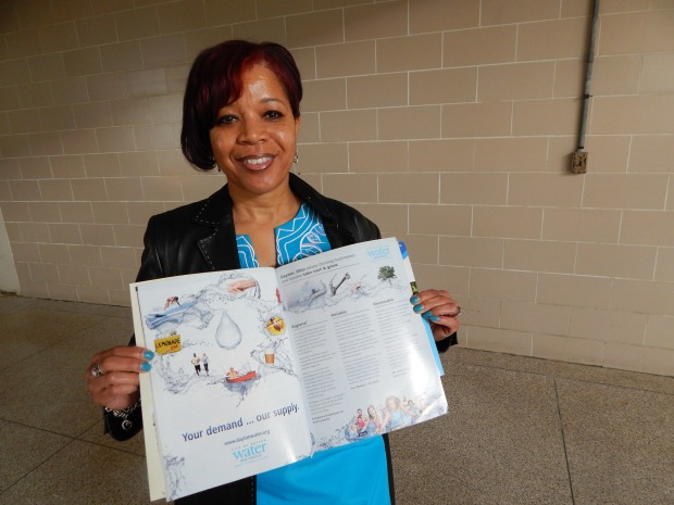 Karen Thomas, the city of Dayton's full-time water marketer, holds up a brochure advertising Dayton's water supply. (Lewis Wallace)