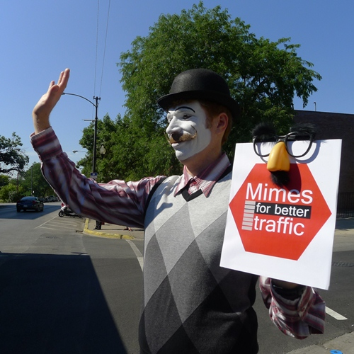Eliot Monaco displays a friendly gesture so as not to spook pedestrians who may be afraid of mimes. (WBEZ/Jennifer Brandel)
