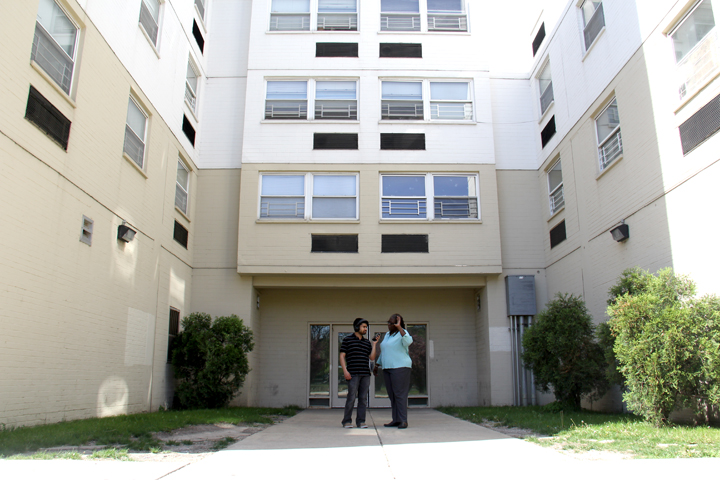 Tanveer Ali, left, and Crystal Palmer stand in her complex's courtyard. She says she could never live in the taller building, as she prefers her courtyard apartment. (WBEZ/Logan Jaffe)
