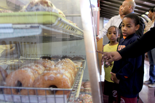 The Williams family picks out their favorite doughnuts at Dat Donut in Chicago's Chatham neighborhood. The Williams family joined Curious City on its first ever doughnut crawl to help decide which privately-owned doughnut shop is the best. (Logan Jaffe/WBEZ)
