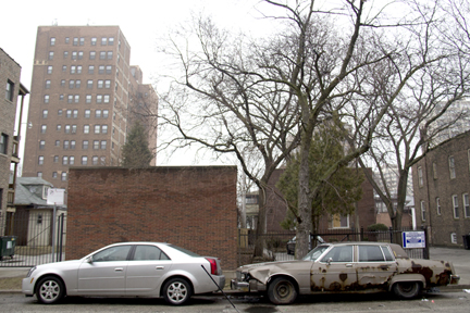 A study in contrasts on Coles Avenue is evident in other kinds of property, too. Here two cars tell two very different stories. (WBEZ/Logan Jaffe)