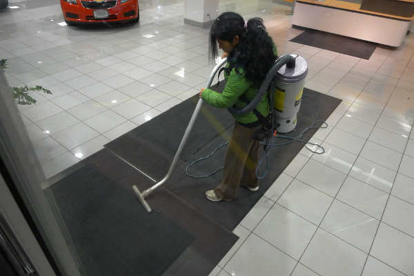 A CleanNet janitor works after hours in a Chicago-area car dealership. Treated like a franchisee, she says her pay amounts to less than Illinois's minimum wage. (WBEZ/Chip Mitchell)