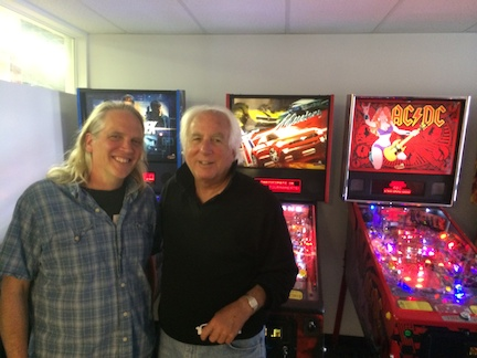 Stern Pinball CEO Gary Stern poses with question-asker Kevin Schramer and some of his company's machines. Stern has worked in the pinball industry for more than 50 years. (WBEZ/Mickey Capper)