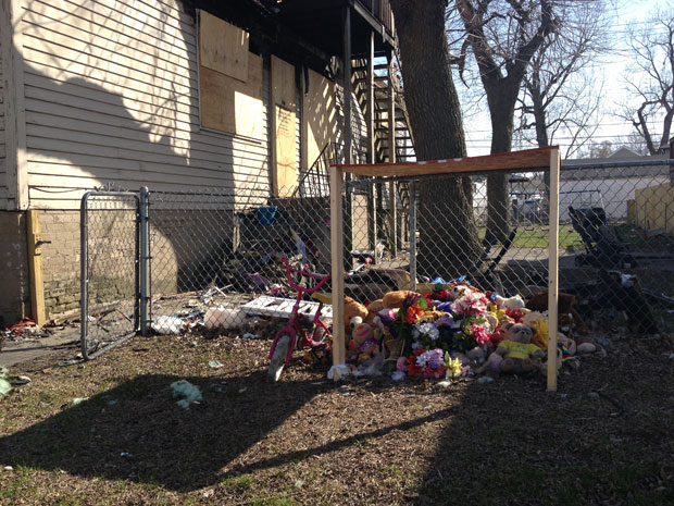 Teddy bears and other mementos remain outside the house months after the fire. The house is scheduled to be demolished soon.