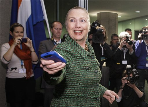 In this Dec. 8, 2011, file photo, then-U.S. Secretary of State Hillary Rodham Clinton hands off her mobile phone after arriving to meet with Dutch Foreign Minister Uri Rosenthal at the Ministry of Foreign Affairs in The Hague, Netherlands. Clinton emailed her staff on an iPad as well as a BlackBerry while secretary of state, despite her explanation that she exclusively used a personal email address on a homebrew server so she could carry a single device, according to documents obtained by The Associated Press. (AP Photo/J. Scott Applewhite, Pool/File)