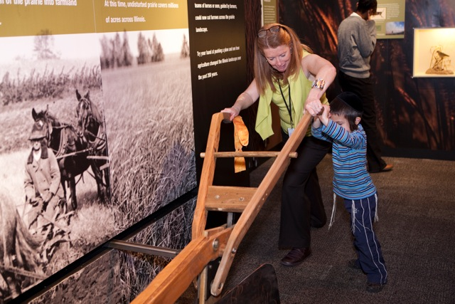 The Peggy Notebaert Nature Museum's President and CEO Deborah Lahey pushes a 19th-century plow replica with an exhibit guest. (Peggy Notebaert Nature Museum)