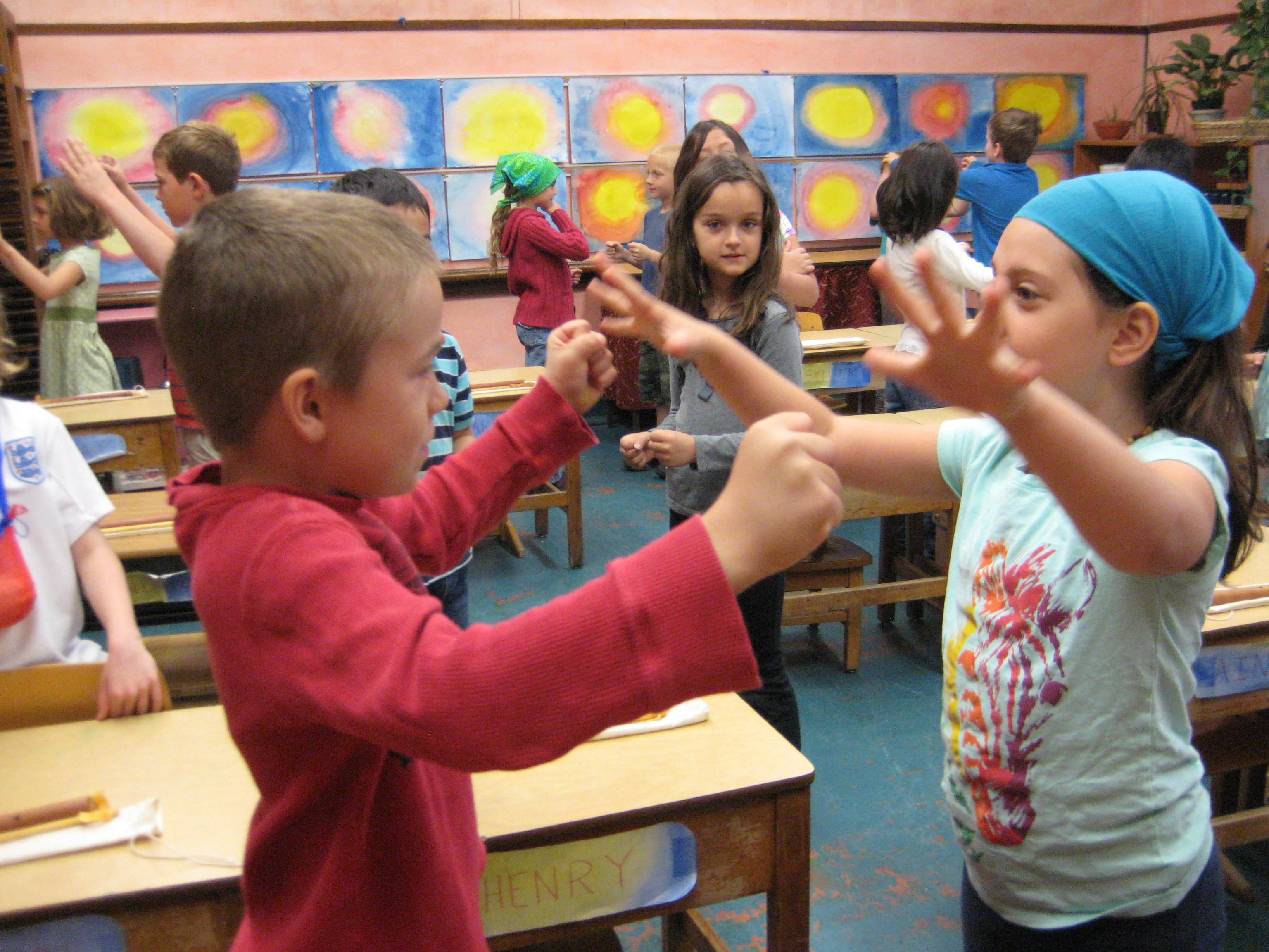 Gil Ron and Eve Thiry play scissors, paper, rock as part of their morning work at the Chicago Waldorf School. The school believes movement—including singing and dance—help children learn vocabulary and the rhythm of language.  (Linda Lutton/Front and Center)