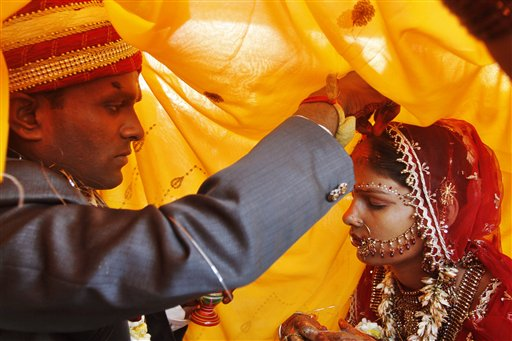 A groom puts red Sindoor powder on his bride's head as part of a ritual during a marriage ceremony in Allahabad, India. (AP/Rajesh Kumar Singh)