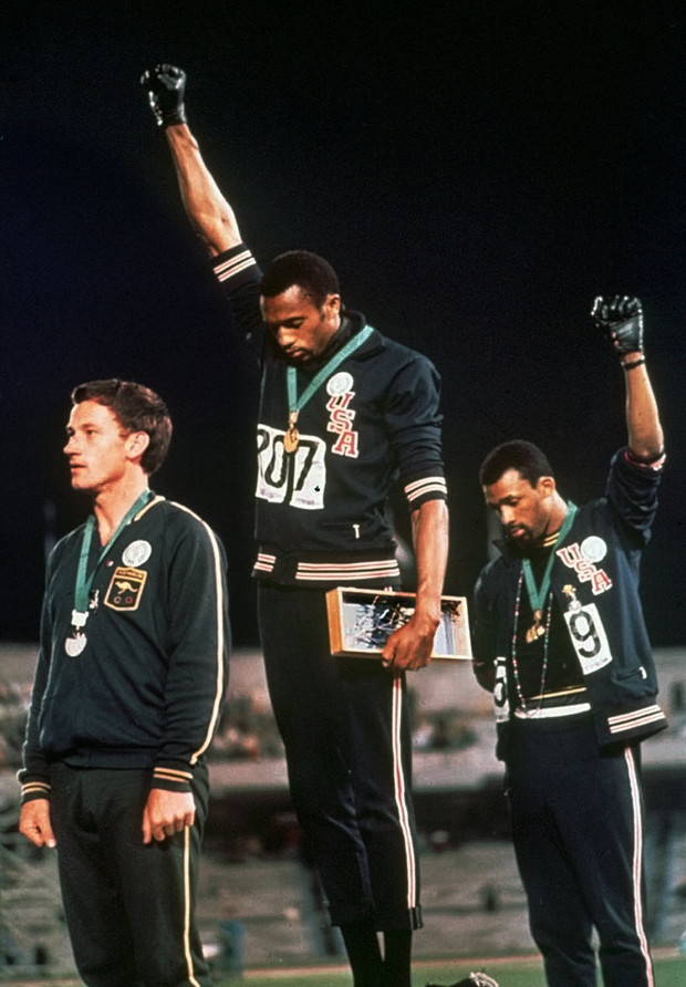 In this 1968 photo, Tommie Smith, center, and John Carlos, right, stare downward with their fists in the air during the 'Star Spangled Banner' after receiving the gold and bronze medals for the 200 meter run. (AP Photo)