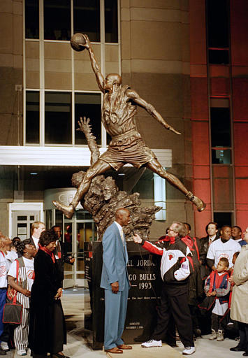 Chicago Bulls' star Michael Jordan stands next to a 12-foot bronze statue of himself unveiled outside the United Center in Chicago, Ill., Nov. 1, 1994, during a salute to Jordan by the Bulls.  At left is Jordan's mother Deloris.  (AP Photo/John Zich)
