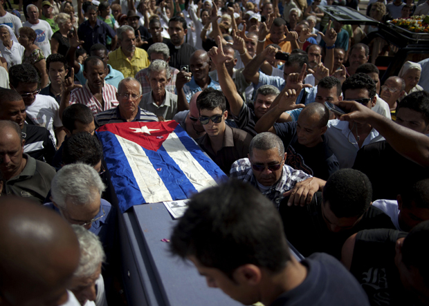 Friends and family of the late Cuban activist Oswaldo Paya carry his flag draped coffin during his burial at a cemetery in Havana Tuesday. Paya, 60, gained international fame as the lead organizer of the Varela Project, a signature-gathering drive asking authorities for a referendum on guaranteeing rights such as freedom of speech and assembly. (AP/Ramon Espinosa)