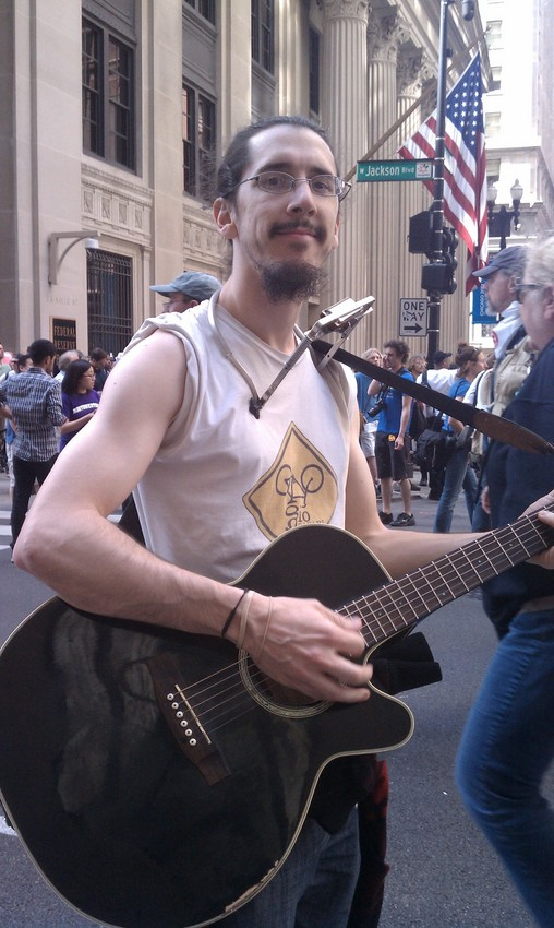 Protester Gio Andollo came to Chicago with his guitar in hand. (WBEZ/Niala Boodhoo)