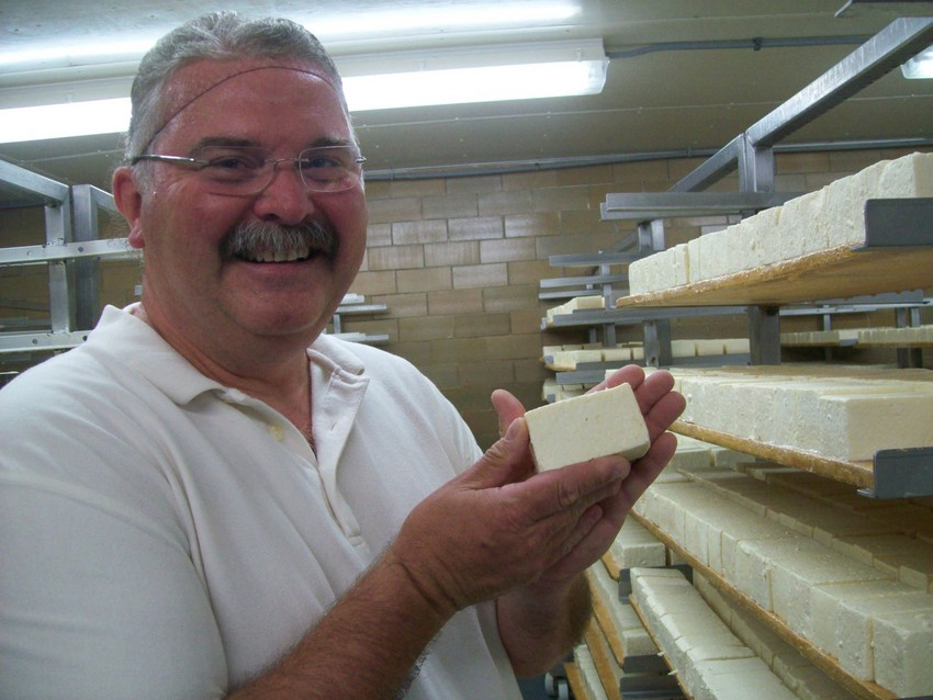 Myron Olson, Master certified Limburger-maker, puts the stink on the Limburger in the curing cellar. (Photo by Nina Barrett)