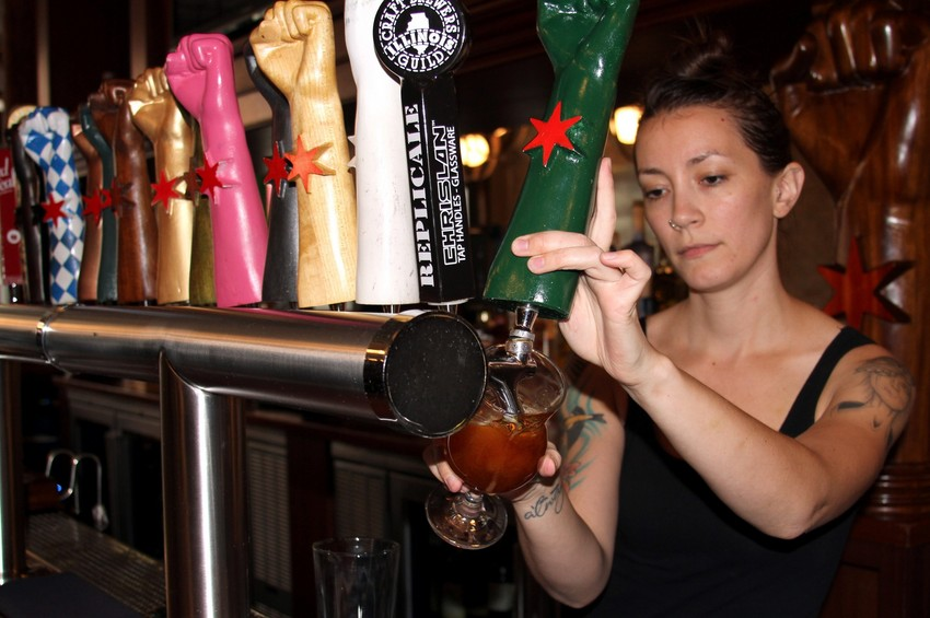 Bartender Alyssa Cornett pours a beer at Revolution Brewing in Logan Square. (Tricia Bobeda/WBEZ)