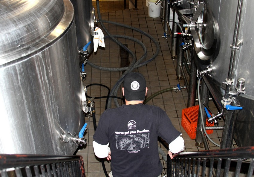 Head brewer Wil Turner sanitizes tanks at Revolution Brewing in Logan Square. (Tricia Bobeda/WBEZ)
