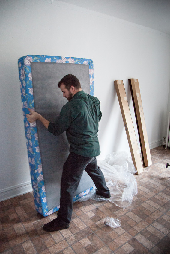 Lowell Wyse did more than ask our Curious City question. Here, he helps set up a bed in a refugee family's apartment. (WBEZ/Shawn Allee)