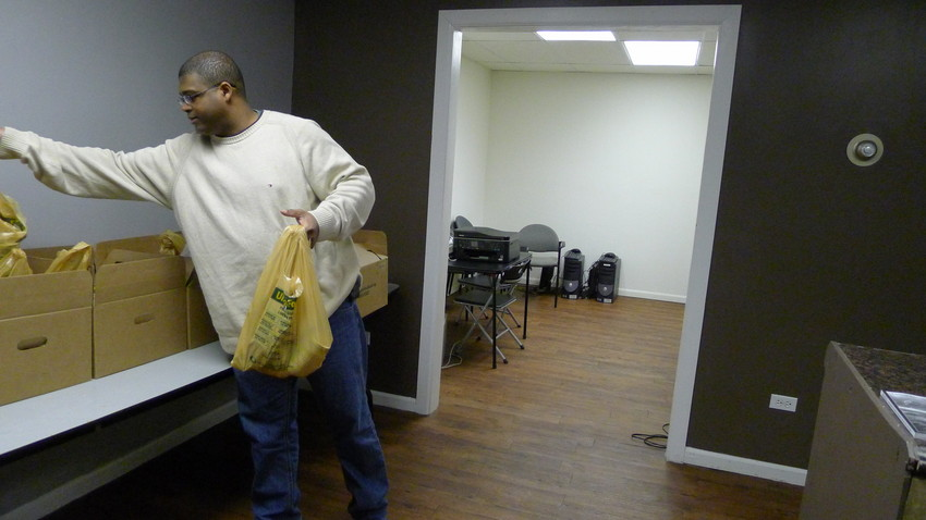 Homer Bizzle reorganizes his small food pantry for veterans. (WBEZ/Lewis Wallace)