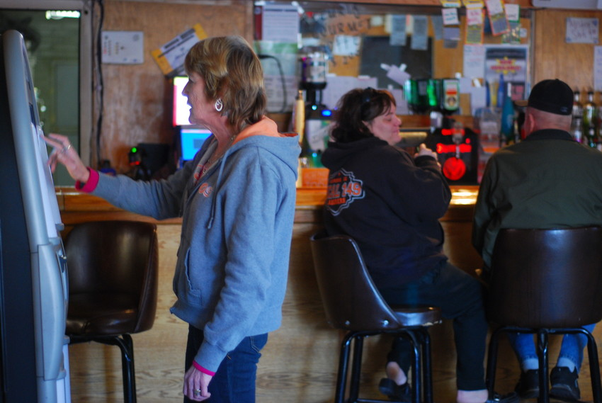 Ronda Bally puts on music at the Stumble Inn in Godley, down the road from the Braidwood plant. (WBEZ/Lewis Wallace)