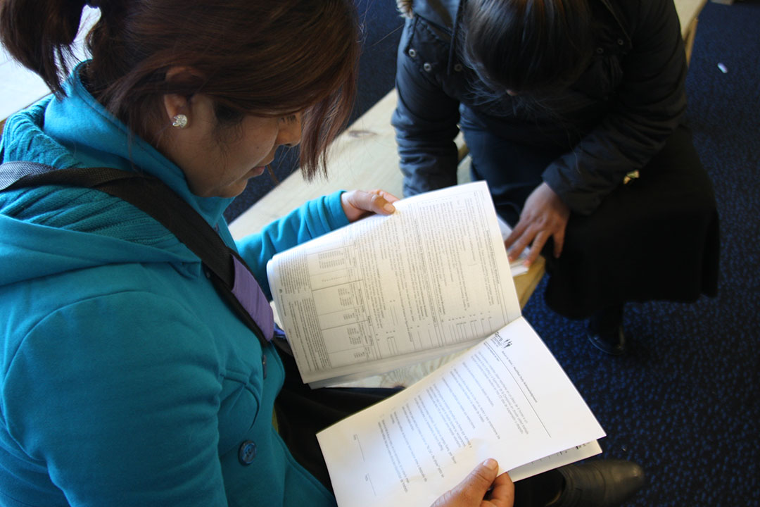 Women fill out job applications at a Ron's Staffing Services office on Chicago's Southwest Side. Ron's assigned Carlos Centeno to the Raani Corp. factory, where he suffered fatal burns. (WBEZ/Logan Jaffe)