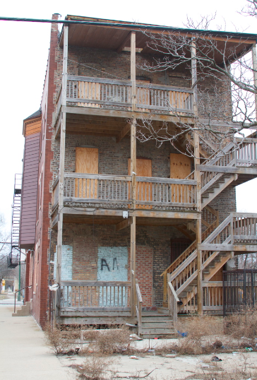 """A neighbor of this Englewood apartment building who called himself """"Big Homie"""" said he felt safer after the building was recently boarded up. (WBEZ/Tricia Bobeda)"""