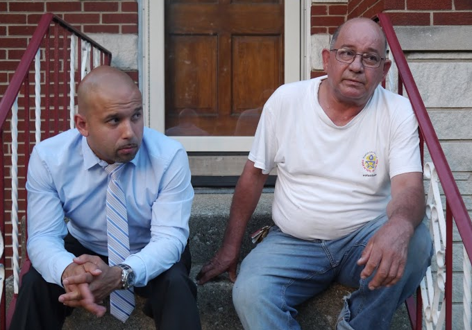 Salvador Nevarez sitting on the front stoop of his home near Midway Airport with his son, Alonzo. (WBEZ/Robert Wildeboer)