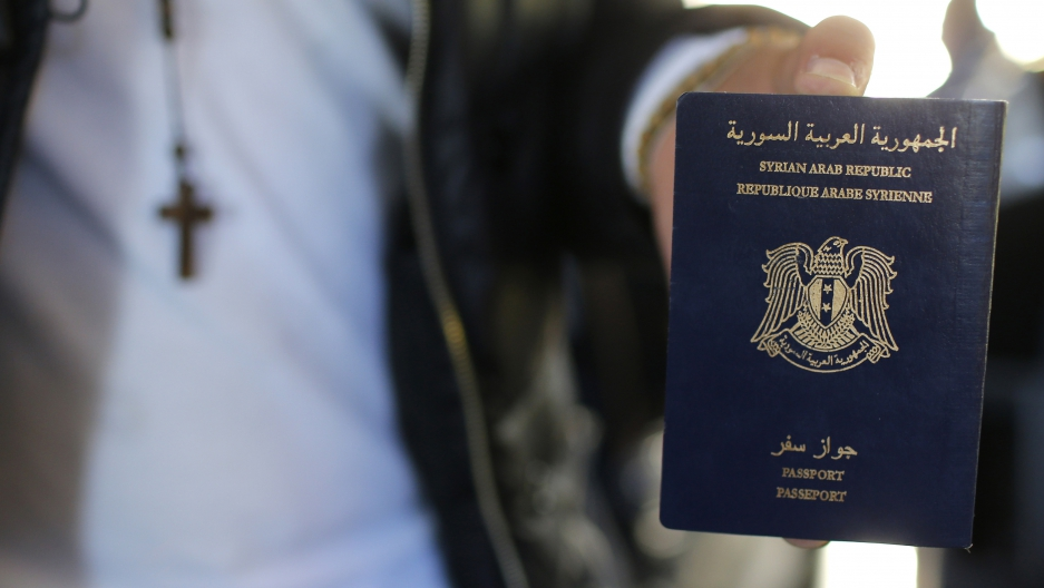 Syrian refugee Ghassan Aleid displays his Syrian passport at a terminal at the Charles-de-Gaulle Airport in Roissy, France. (Stephane Mahe/Reuters)
