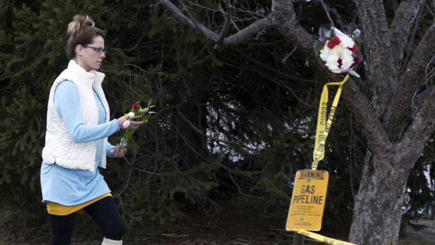 A woman places flowers at a Cracker Barrel restaurant where people were gunned down in the parking lot amid an hours-long shooting spree in Kalamazoo, Mich. (Tasos Katopodis/Getty Images)