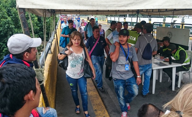 These people have just walked across the bridge from Venezuela to Colombia, where the Colombian immigration authorities are on duty. Many people live on one side and work on the other, crossing so frequently they don't have to register with officials each time. (Vladimir Solano/NPR)