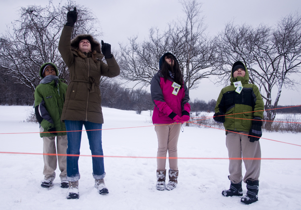"The ""web of life"" exercise, wherein kids map out ecological relationships using orange rope, is interrupted by the flight of a Cooper's hawk overhead. Cheryl McGarry of the Forest Preserve District of Cook County, points to the bird. (WBEZ/Chris Bentley)"