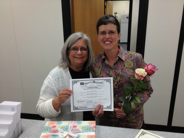 Barb McMillan, left, and her wife Roseann Szalkowski, of northwest suburban Roselle, pose with their new marriage license at the DuPage County Clerk's Office on Monday. (WBEZ/Alex Keefe)