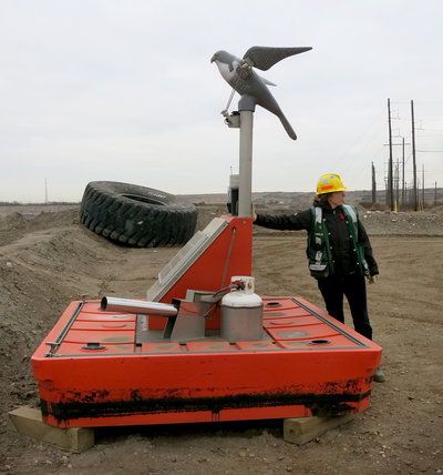 Ainslie Campbell, environmental sustainability manager for Shell's oil sands operation, demonstrates a device to keep migrating birds out of grimy water that collects at reclamation sites. (Jeff Brady/NPR)