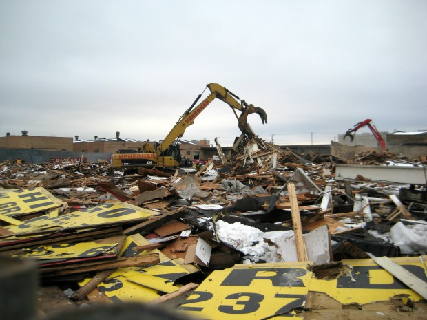 A bulldozer works to demolish the Rubenstein Lumber Yard at 5321 W. Grand, where Noble Street Charter Network is proposing to build a school. Protesters complained Monday that the demolition was taking place even before the school board vote. (WBEZ/Linda Lutton)