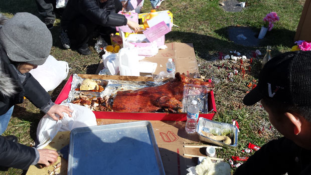 Many Chinese families bring gifts of food when they visit their ancestors at Mount Auburn Memorial Park in Stickney. (WBEZ/MONICA ENG)