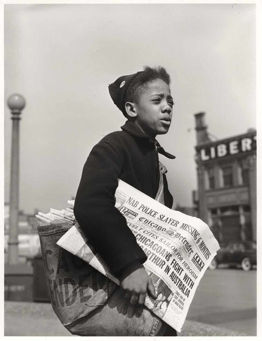 Portrait of a young African American boy selling the Chicago Defender on a street corner on Chicago's South Side, April 1942. The boy carries a full bag of the daily newspaper and holds one in his hand to flog. (Jack Delano/International Center of Photography)