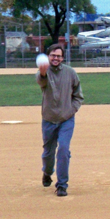 Curious citizen Derek Stiles tries his first pitch with a 16-inch softball.