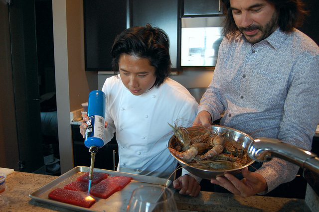 Embeya Executive Chef Thai Dang searing tuna, with partner Attila Gyulai holding blue prawns (WBEZ/Louisa Chu)