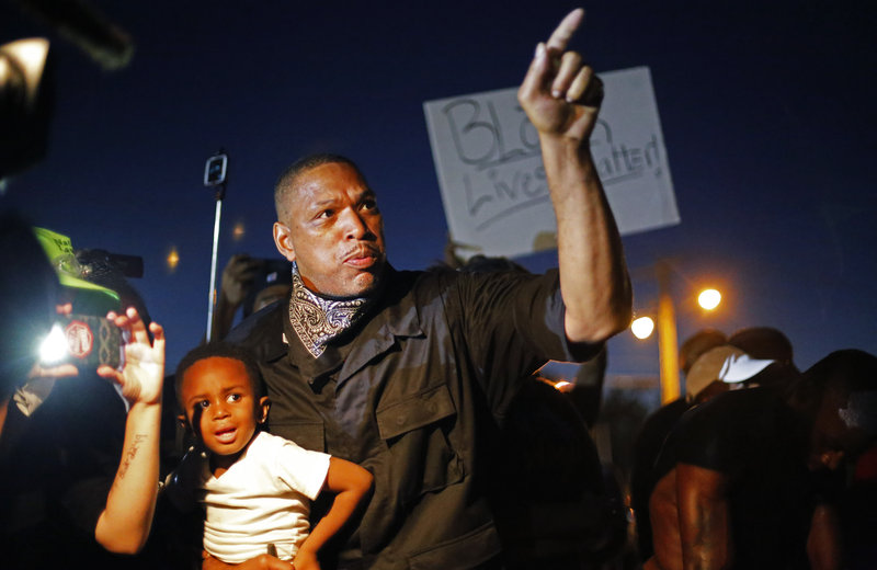 A father holds his son as he takes part in a demonstration in Ferguson, Mo., on Monday night. Police arrested more than 20 people in the city's streets Monday night; no violence or damage was reported. (Jim Vondruska/Xinhua/Landov)