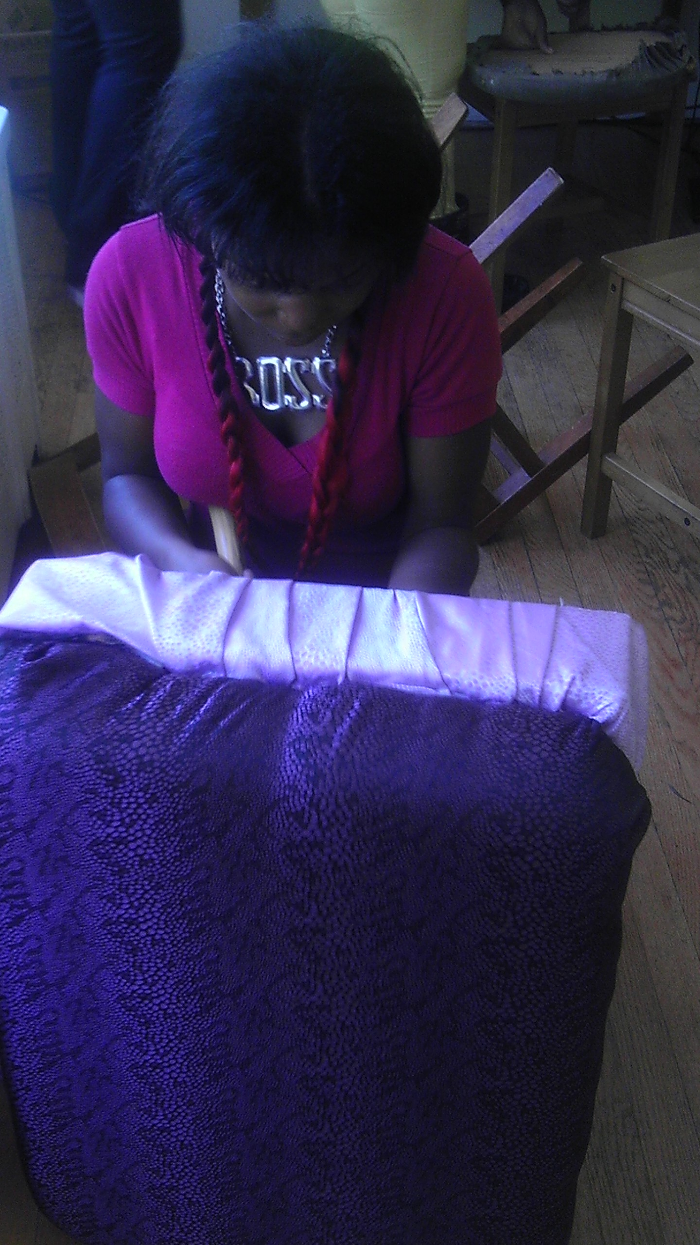 Laquisha Clinton refurbishes a foot stool as part of Teena's Legacy. (Natalie Moore/WBEZ)