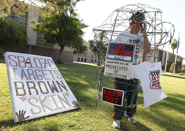 Jorge Mendez joins others from Promise Arizona to protest the upcoming U.S. Supreme Court decision on Arizona's immigration law on Friday. (AP/File)