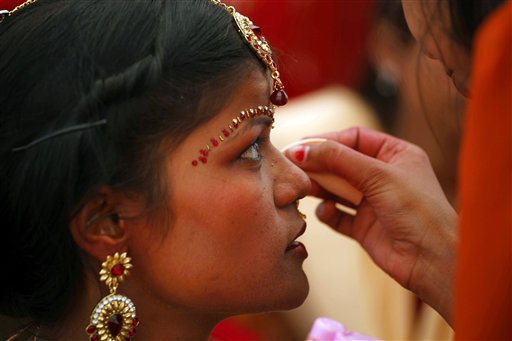 A family member applies makeup on an Indian bride before a ritual at a mass marriage in Allahabad, India. (AP/Rajesh Kumar Singh)