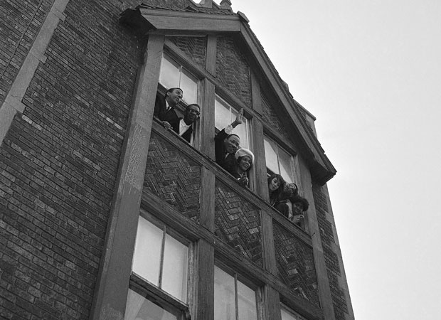 Dr. Martin Luther King, Jr. and his wife Coretta Scott King wave to crowd in street from center window of a third-floor walk-up apartment he rented in a slum area on Chicago's West Side, Jan. 26, 1966. Dr. King announced he will spend two or three days a week in Chicago directing a campaign against slum conditions. Mrs. King said she would stay in the flat for tonight only, and then return to Atlanta. Dr. King pays $90 a month rent for the four-room apartment. (AP Photo/Edward Kitch)