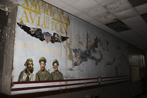 The Eliot building is falling apart, but hints of the past still line the surface — like this old mural visible through the peeling paint. (Tim Lloyd/ St. Louis Public Radio)