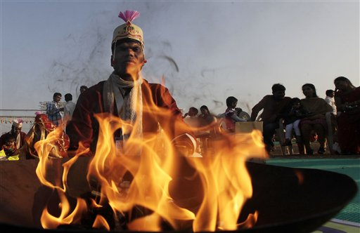 An Indian groom sits behind a flame during a ritual at a Hindu wedding ceremony outside of Mumbai. (AP/Rajanish Kakade)