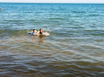 Children take a dip in Lake Michigan at Oak Street Beach despite the bacteria advisory. (WBEZ/Jewell Washington)