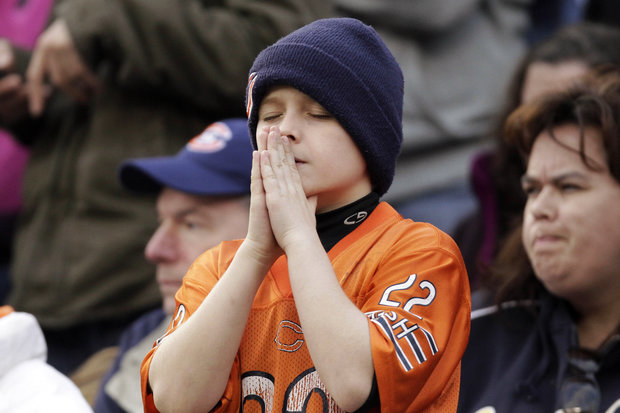 A Bears fan's prayer is not answered in the OT loss. (AP Photo/Nam Y. Huh)
