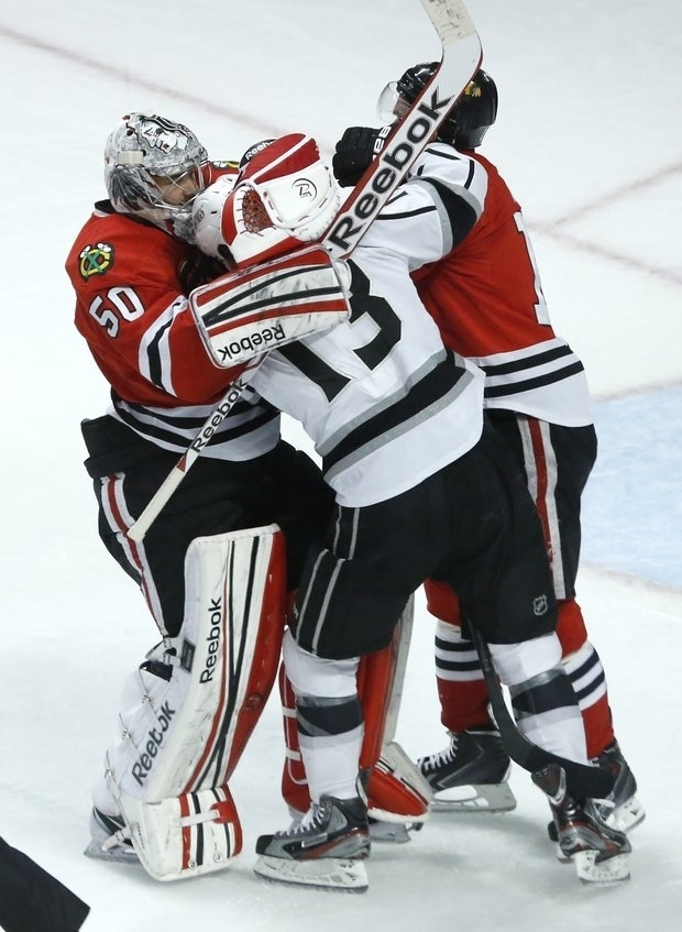 Hawks goalie Corey Crawford helps his Captain. (AP)