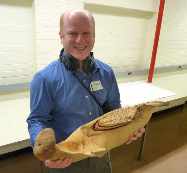 Gabriel Spitzer holding an elephant jaw bone. (WBEZ/Michael De Bonis)