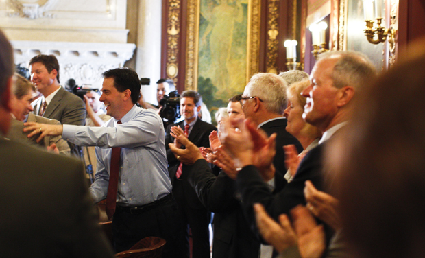 Wisconsin Gov. Scott Walker, center, is greeted by his cabinet and staff a day after he beat Milwaukee Mayor Tom Barrett in a recall election. (AP/Andy Manis)