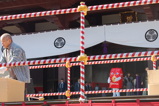 Tohato Caramel Corn mascot waits to throw lucky food at Zojoji temple in Tokyo, Japan on Setsubun (WBEZ/Louisa Chu)